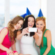 Three smiling women in hats having fun with camera — Stok fotoğraf