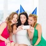 Three women in hats having fun with camera — Stok fotoğraf
