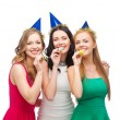Three smiling women in hats blowing favor horns — Стоковая фотография