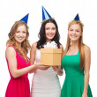 Three smiling women in blue hats with gift box — Стоковая фотография