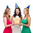 Three smiling women in blue hats with gift box — Stock Photo