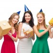 Three smiling women in blue hats with gift boxes — Lizenzfreies Foto