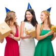 Three smiling women in blue hats with gift boxes — Stock Photo #34575147