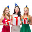 Three smiling women in blue hats with gift boxes — ストック写真