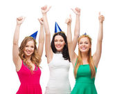Three women wearing hats and showing thumbs up — Stockfoto