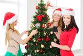 Women in santa helper hats decorating a tree — Stockfoto