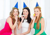 Three smiling women in hats blowing favor horns — Foto Stock