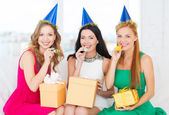 Three women wearing hats with gifts blowing horns — Stock Photo