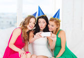 Three women in hats having fun with camera — Stock Photo
