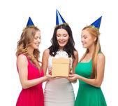 три улыбающихся женщин в голубые шляпы с подарочной коробке — Стоковое фото