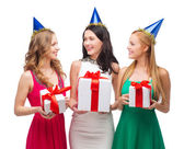 Three smiling women in blue hats with gift boxes — Stock fotografie