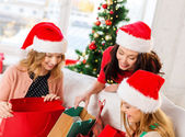 Women in santa helper hats with shopping bags — Stock Photo