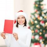 kobieta w santa hat pomocnika z pusta czerwona kartka — Zdjęcie stockowe