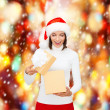 Surprised woman in santa helper hat with gift box — Stock Photo