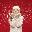 Happy girl in winter clothes blowing on palms — Foto Stock