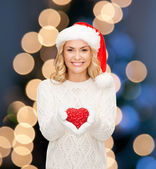 Smiling woman in santa helper hat with red heart — Stock Photo