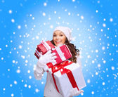 Woman in sweater and hat with many gift boxes — Stock Photo