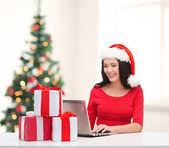 Mulher com caixas de presente e computador portátil — Fotografia Stock