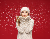 Happy girl in winter clothes blowing on palms — Stock Photo