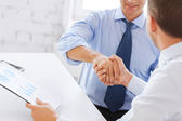 Businessmen shaking hands in office — Stock Photo