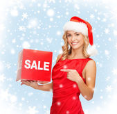 Woman in santa helper hat with red sale sign — Stock Photo