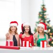 Smiling women in santa helper hats with gift boxes — Stockfoto