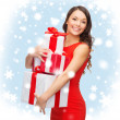Smiling woman in red dress with many gift boxes — Stock Photo #34767023