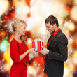 Smiling woman and man with gift box — ストック写真