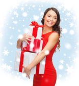 Smiling woman in red dress with many gift boxes — Stock Photo