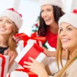 Women in santa helper hats with many gift boxes — Стоковая фотография