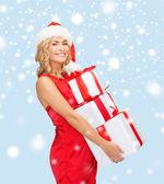Woman in santa helper hat with many gift boxes — Φωτογραφία Αρχείου