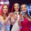 Three smiling women with cocktails and disco ball — Стоковая фотография