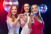 Three smiling women with cocktails and disco ball — Stok fotoğraf