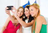 Three smiling women in hats having fun with camera — Foto de Stock