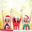 Smiling women in santa helper hats with gift boxes — Stock Photo #34830023