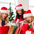 Women in santa helper hats with shopping bags — Stock Photo #34830351