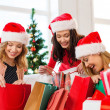 Stock Photo: Women in santa helper hats with shopping bags