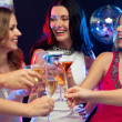 Three smiling women with cocktails in club — Stock Photo #34830771