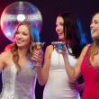 Three smiling women with cocktails and disco ball — Stock Photo #34833111