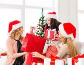 Women in santa helper hats with shopping bags — Stock Photo
