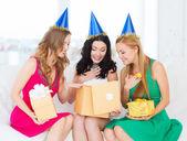 三个微笑妇女在蓝色的帽子与礼品盒 — 图库照片
