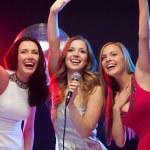 Three smiling women dancing and singing karaoke — Stock Photo #34853307
