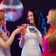 Three smiling women with cocktails and disco ball — Stock Photo