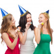 Three smiling women in hats blowing favor horns — Stok fotoğraf