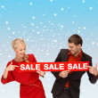 Smiling woman and man with red sale sign — Stock Photo