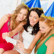 Three smiling women in hats having fun with camera — Stockfoto