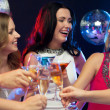 Three smiling women with cocktails in club — Stock Photo #34908269