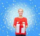 Smiling woman in red sweater with gift box — Stock Photo