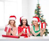 Mulheres sorridentes em chapéus de ajudante de papai noel com caixas de presente — Fotografia Stock