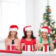 Smiling women in santhelper hats with gift boxes — Stock Photo #34917599
